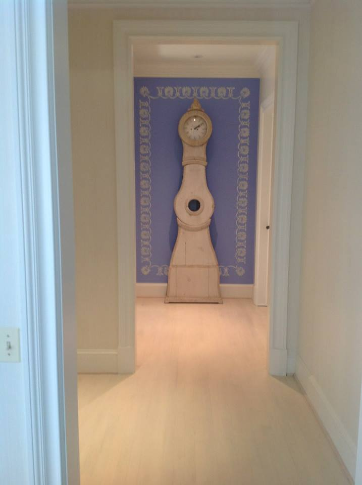 Blue accent wall showcases Gustavian style Swedish grandfather clock. Blue and white pattern hand painted border.
